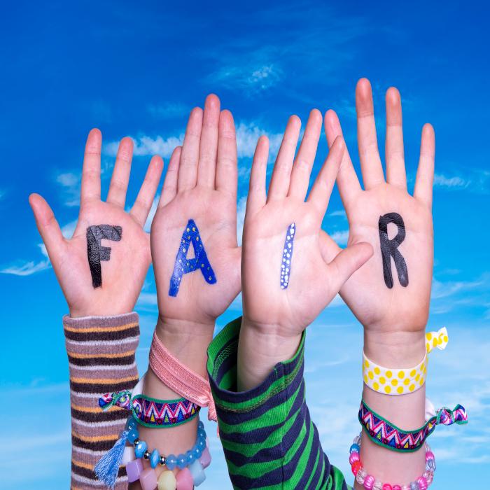 Kinderhände halten die Buchstaben FAIR in den Himmel